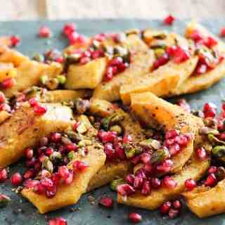 Roasted Acorn Squash with Pomegranate and Pistachios! A simple and delicious Thanksgiving side dish. Recipe via www.gratefulgrazer.com