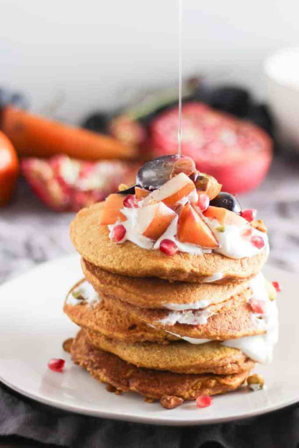 Stack of pumpkin pancakes topped with yogurt and fruit on white plate with drizzle of maple syrup pouring over top.