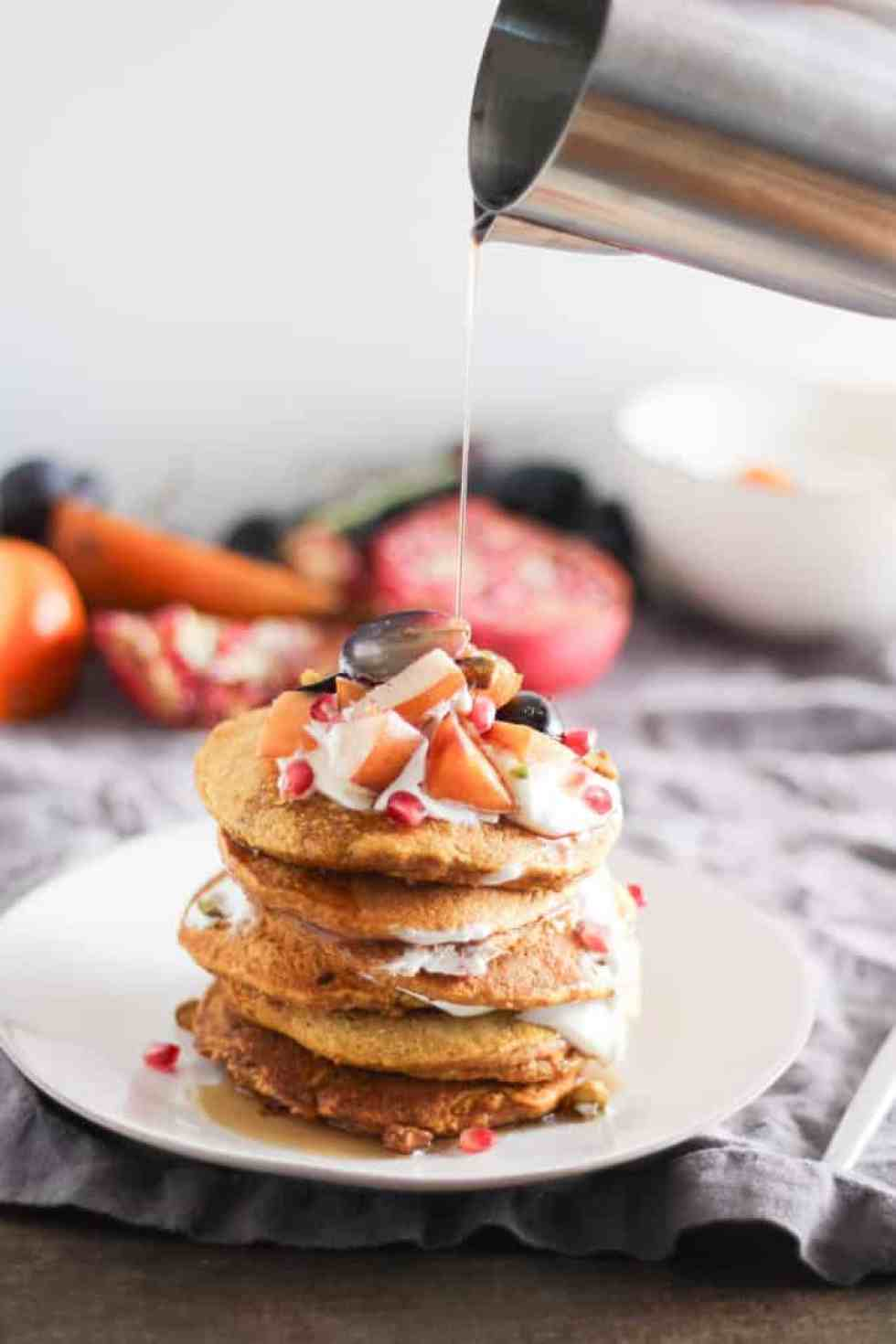 Stack of pumpkin pancakes on white plate with pitcher of syrup pouring over the plate.
