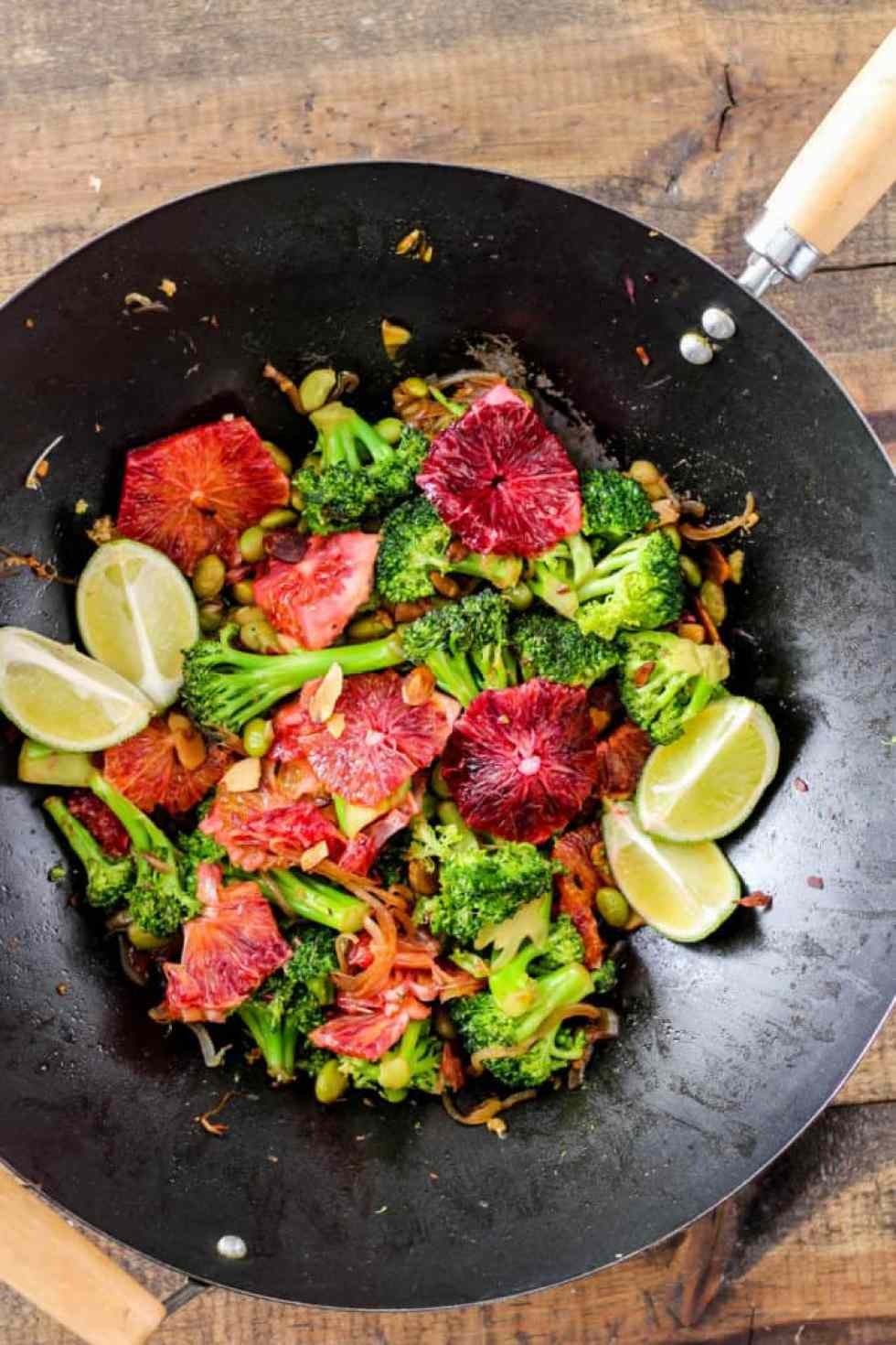 Broccoli Stir-Fry with Blood Oranges in black wok against wood background.