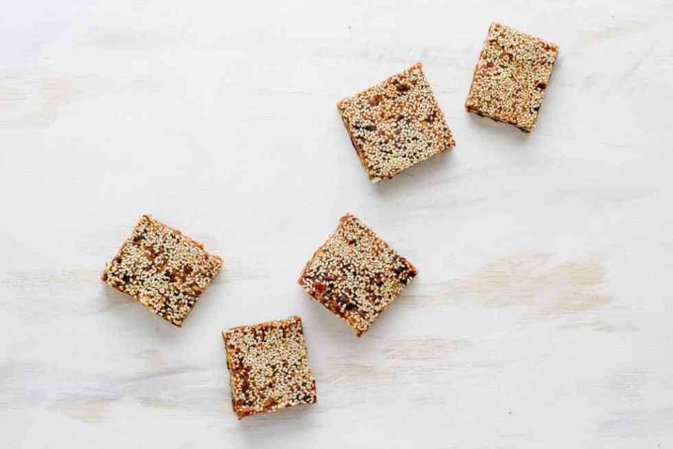 Sesame date bars arranged in curved line against white backdrop.
