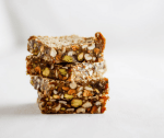 Stack of four sesame date bars with pistachios with white background.