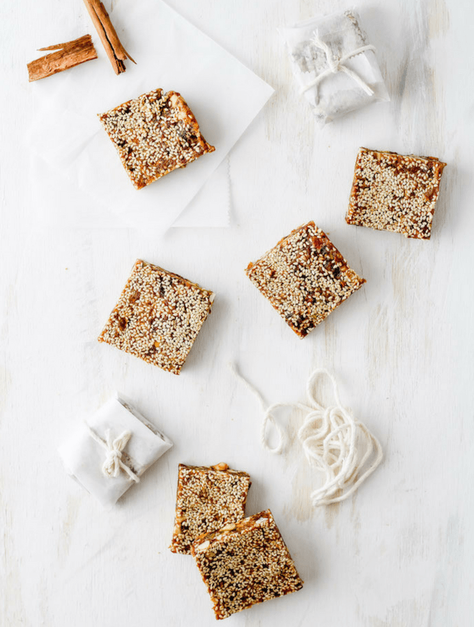 Sesame date bars arranged on a white backdrop. Wrapped in parchment paper and tied with string.