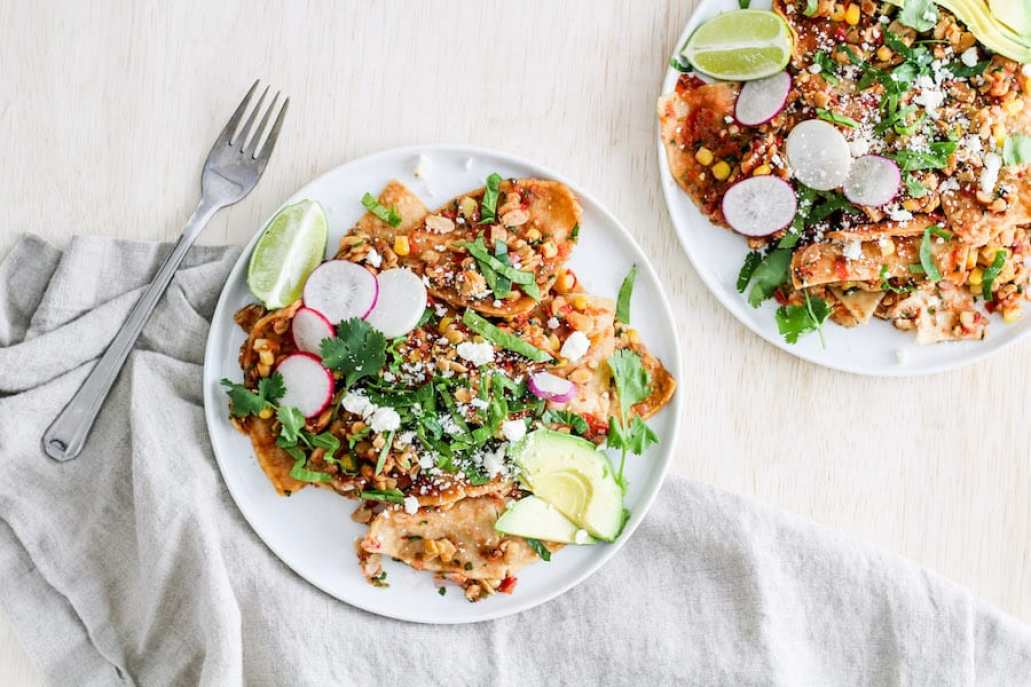 Overhead shot of tempeh chilaquiles on white plates with linen napkin.