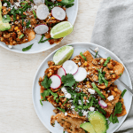 Two white plates of tempeh chilaquiles.