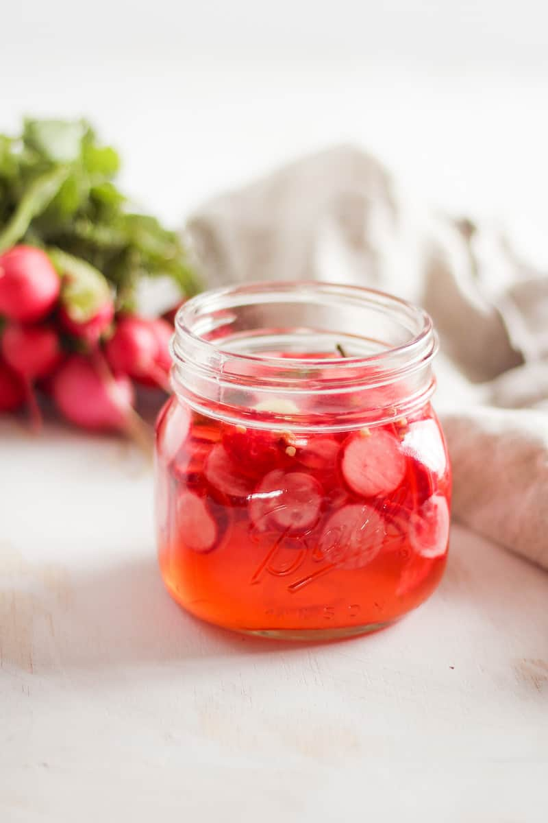Quick-pickled radishes in mason jar with bunch of radishes in background and neutral linen napkin.