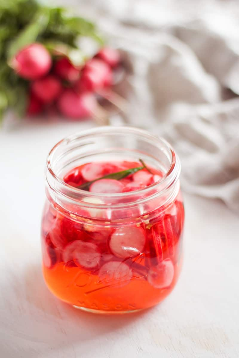Quick-pickled radishes in a mason jar against white backdrop with bunch of radishes in background.