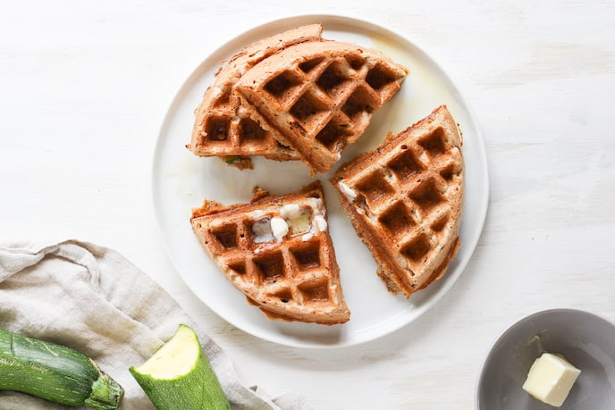 Overhead shot of sliced whole wheat zucchini bread waffles on white plate.