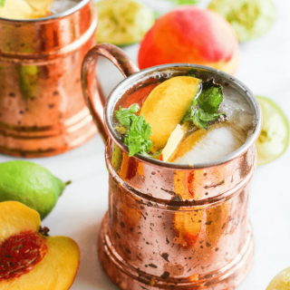 Ginger peach kombucha Moscow mule in copper mug surrounded by peaches and lime on white marble.
