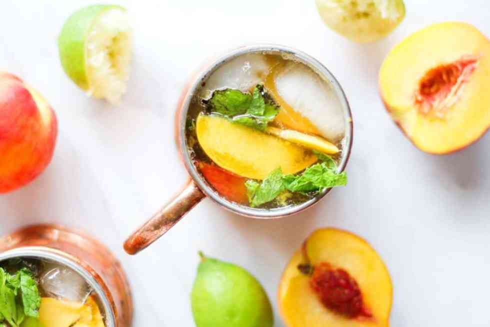 Overhead shot of ginger peach kombucha moscow mule recipe in copper mug on white marble with peaches and lime.