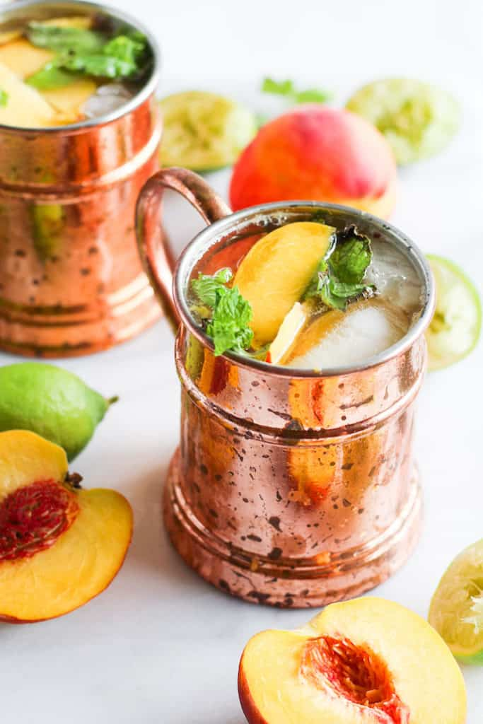 Ginger peach kombucha moscow mules in copper mugs on white marble with peaches and lime.
