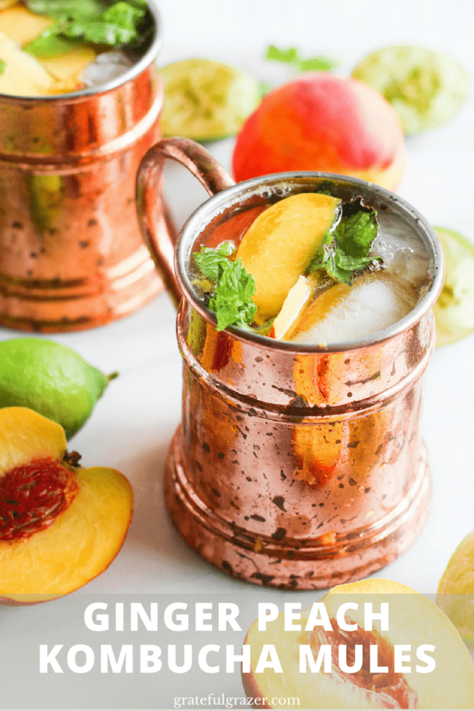 "Ginger peach kombucha Moscow mule in copper mug on white marble surrounded by peaches and lime. Title text reads, ""Ginger Peach Kombucha Mules."""