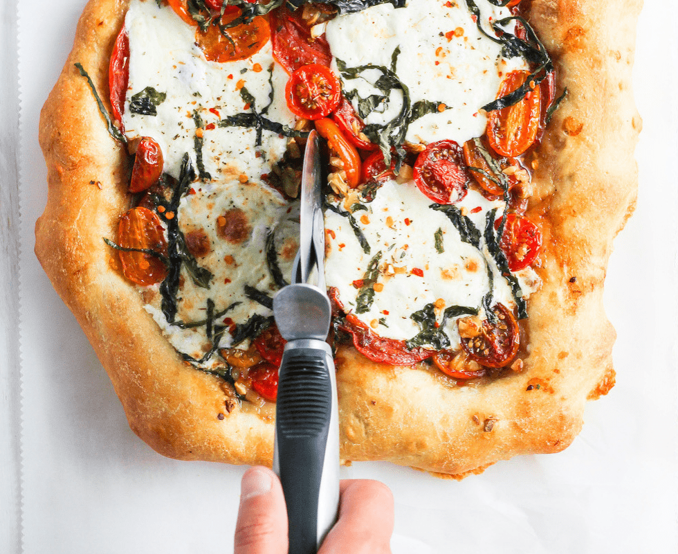 """Tomato pizza being cut with pizza cutter and title text that reads, """"Seasonal Produce Guide."""""""