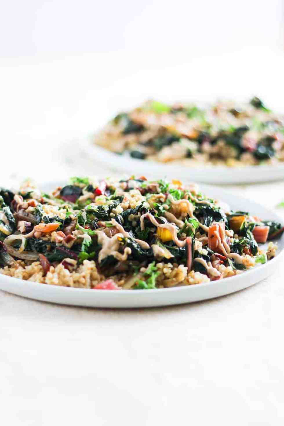 straigt-on shot of toasted freekeh with rainbow chard and tahini sauce on white plate against white background.