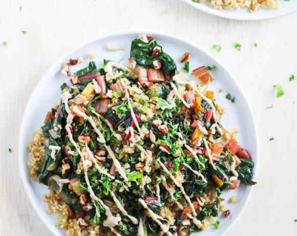 Toasted freekeh with rainbow chard and tahini sauce on white plate against white background.