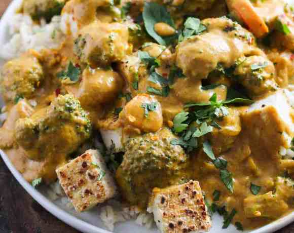Pumpkin curry with crispy tofu and broccoli on white plate against dark wood backdrop.
