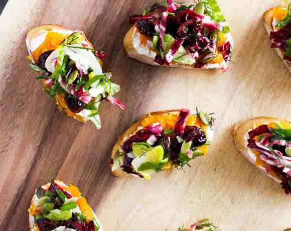 Butternut squash toast with brussels sprouts slaw on wood serving board.
