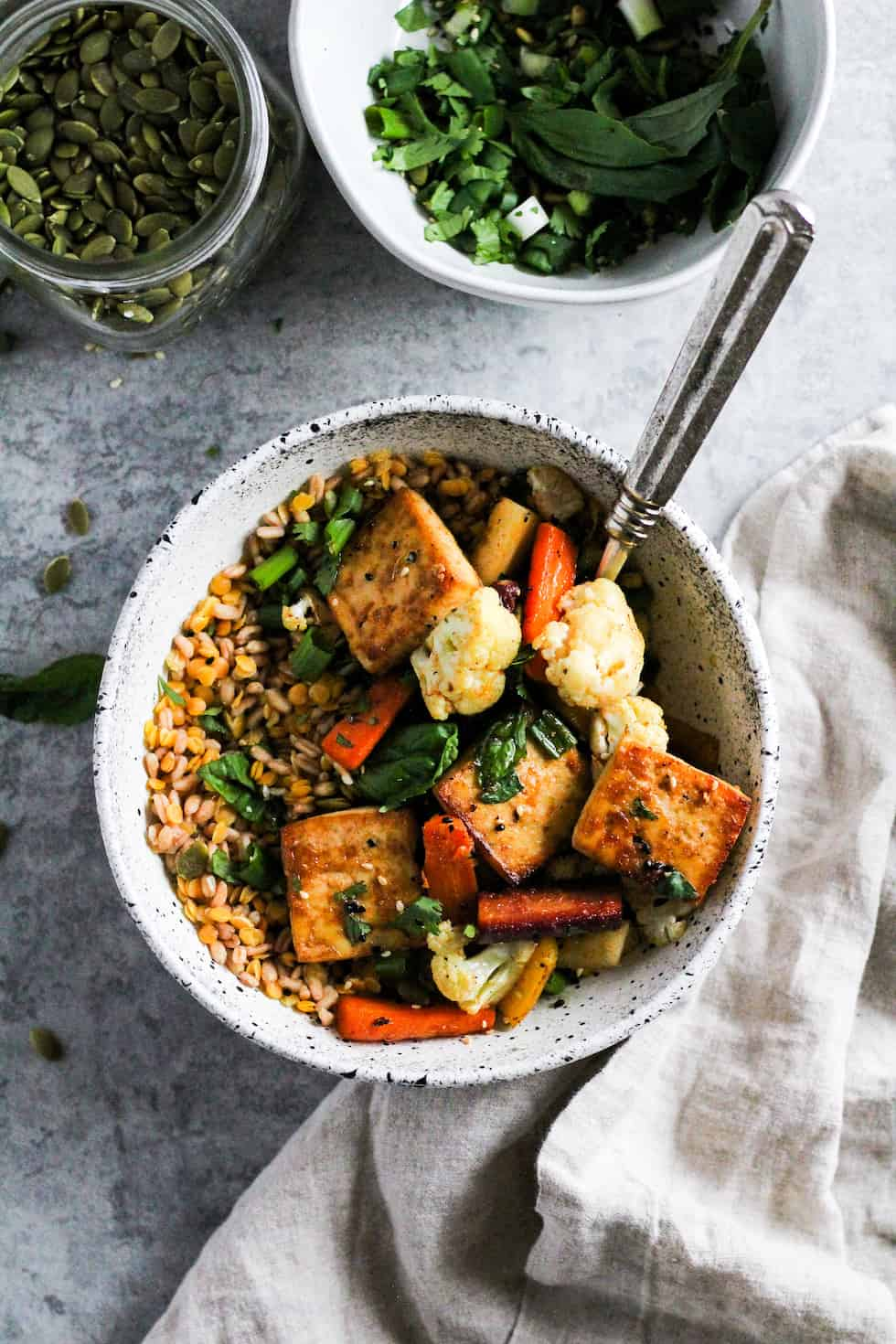 Sheet pan tofu bowls in white stone bowl with linen napkin and grey background.