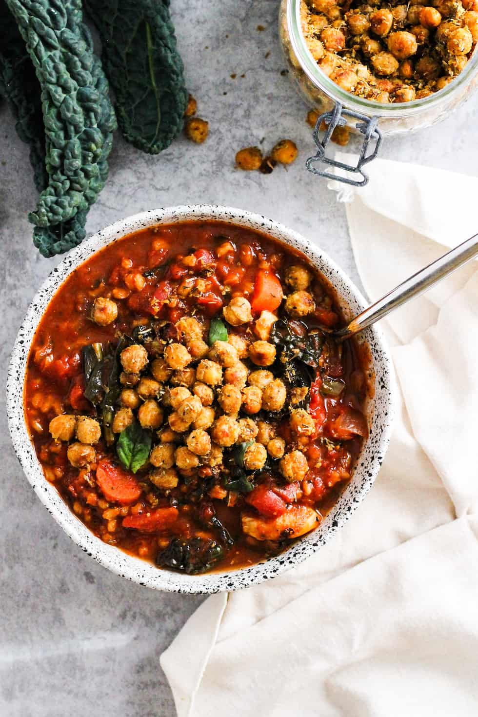 Tomato barley soup in white stone bowl with cream napkin and kale and chickpeas.