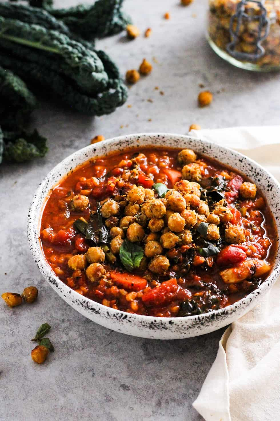 Tomato barley soup with roasted chickpeas in stone bowl with kale and mason jar or chickpeas in the background.