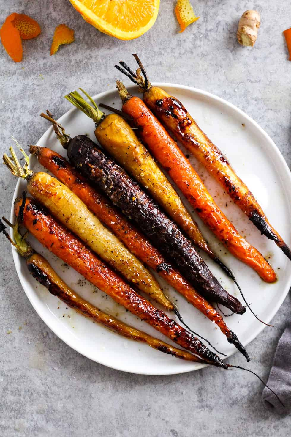 Roasted rainbow carrots on white plate with orange and ginger around the edges.