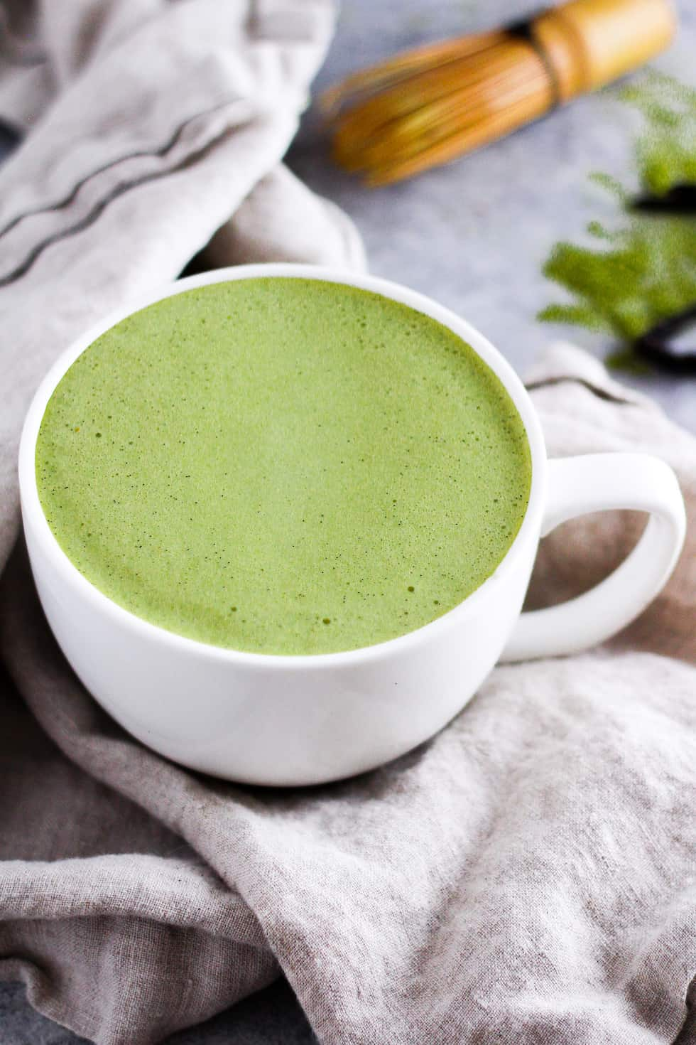 Matcha latte in white mug with cream napkin and whisk in background.