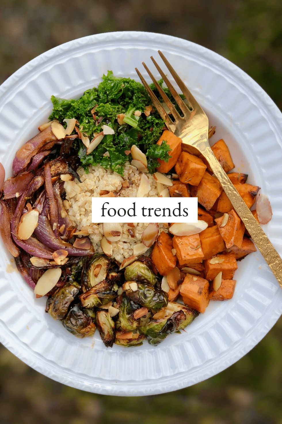Food trends title image with buddha bowl on white plate with gold fork.