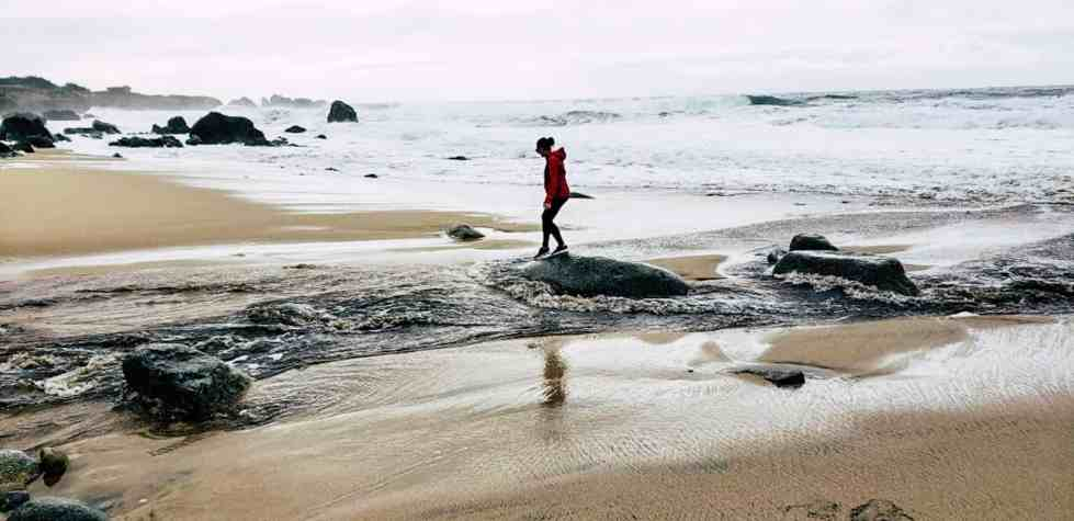 Low-waste travel. Girl waking on beach.
