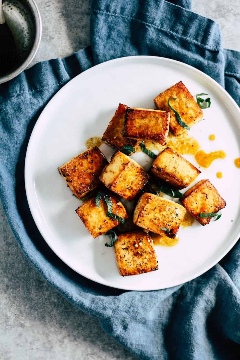 Crispy tofu on white plate with blue napkin and bowl of garlic soy sauce.