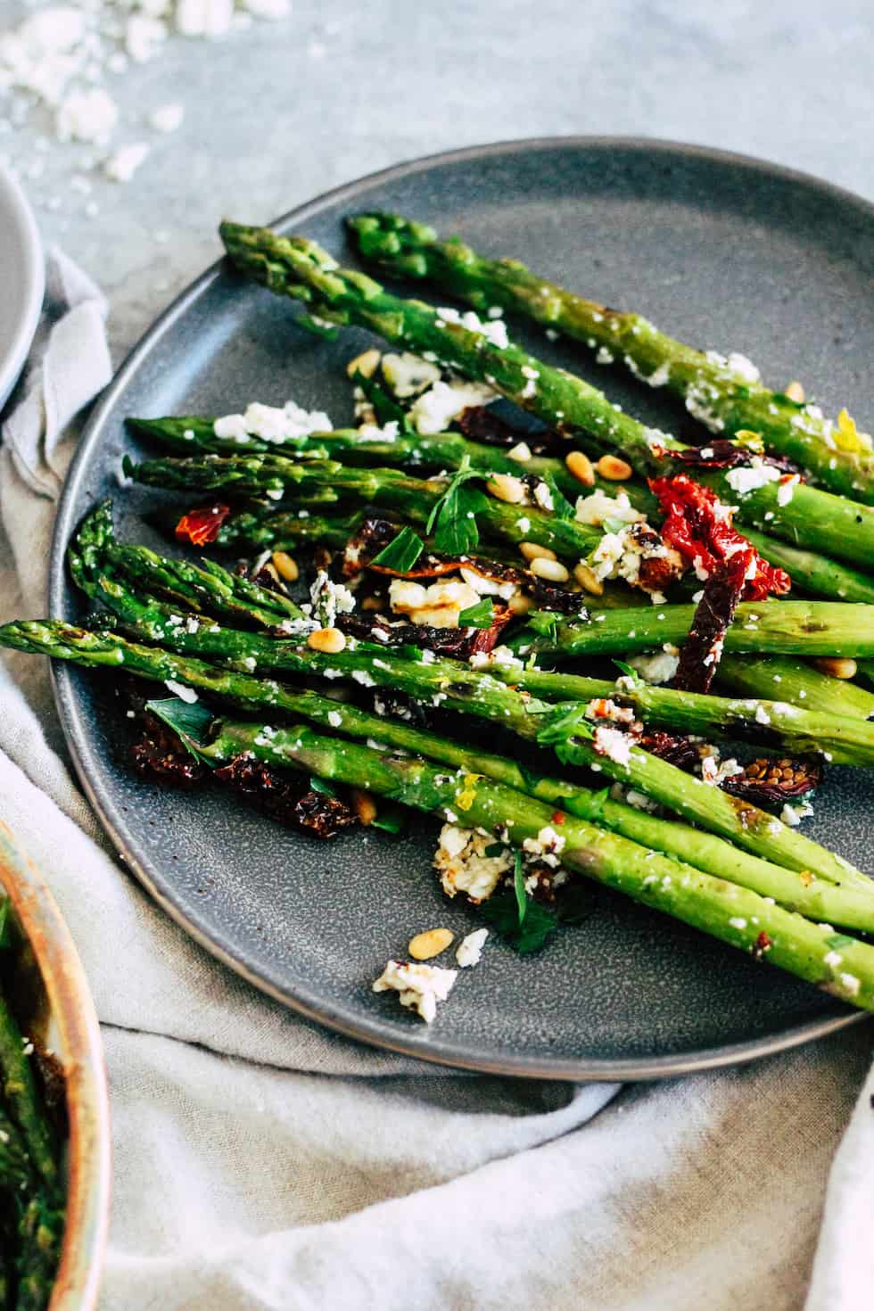 Asparagus spears on a gray plate with sun-dried tomato and feta cheese.