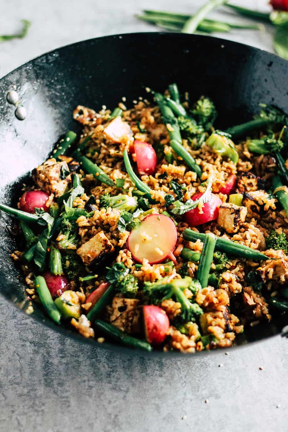 Wok of veggie fried rice with radishes and green beans.