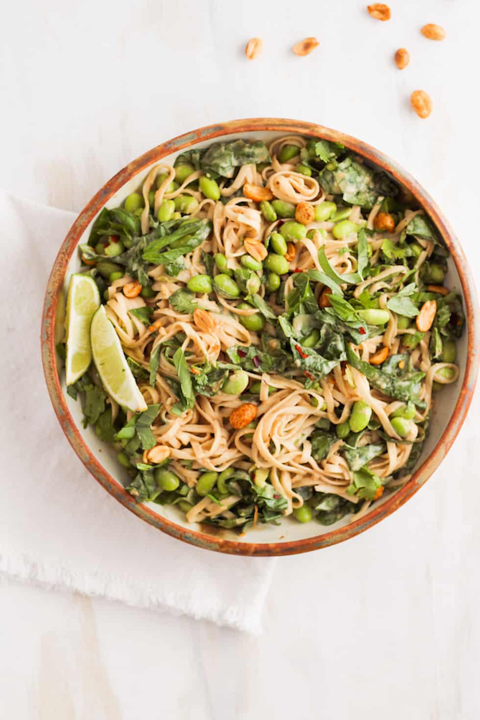 15-minute easy vegetarian peanut noodles in brown ceramic dish.