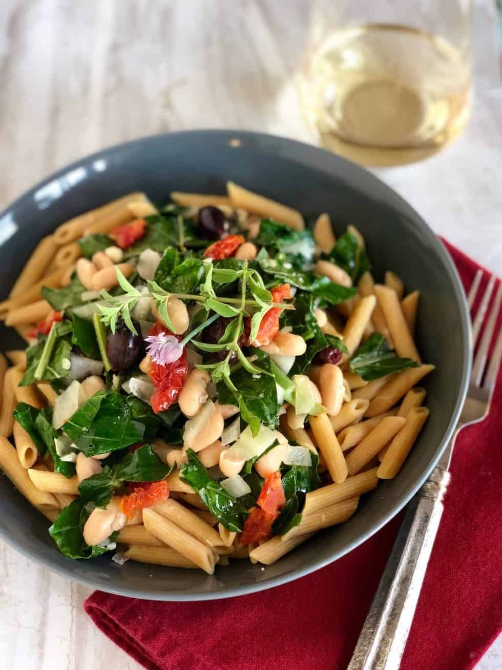 Vegetarian dinner recipes include this penne with white beans in a grey bowl with a red napkin and glass of white wine.