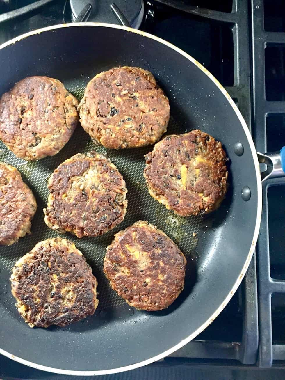 Vegetarian bean burgers in a skillet on a gas stove.