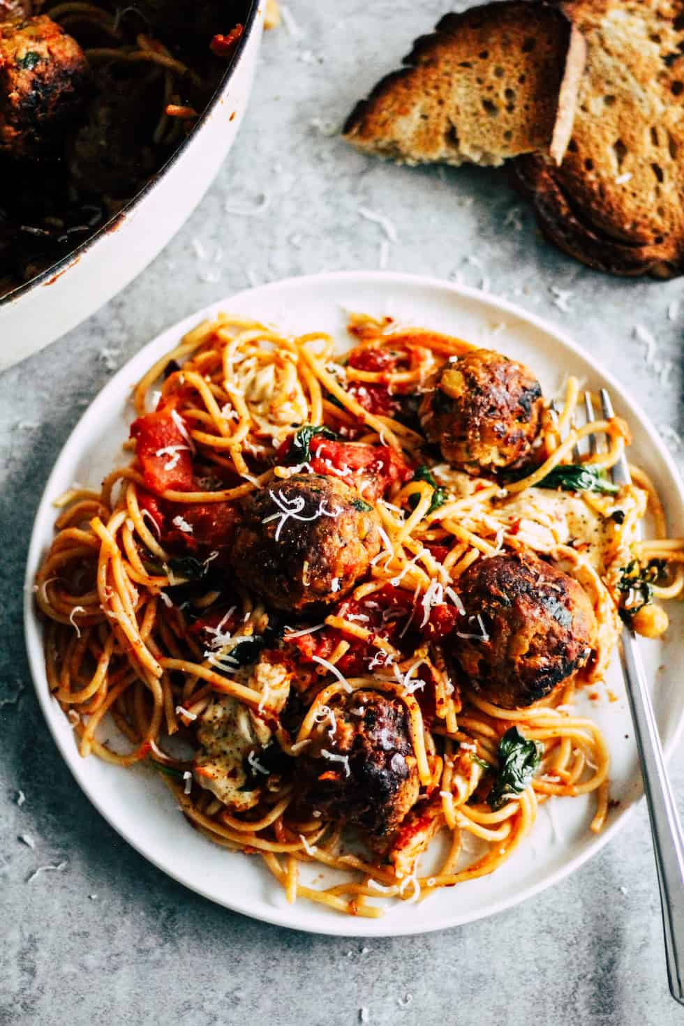 Spaghetti and meatballs on white plate with toasted bread in the background.