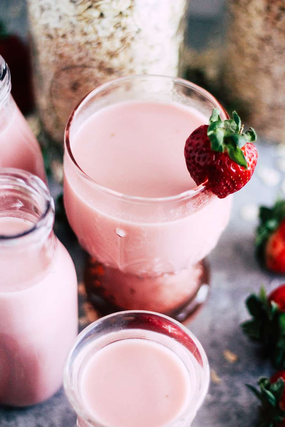 Pink glass filled with strawberry oat milk with a strawberry garnish. Jars of oats and milk jars in background.