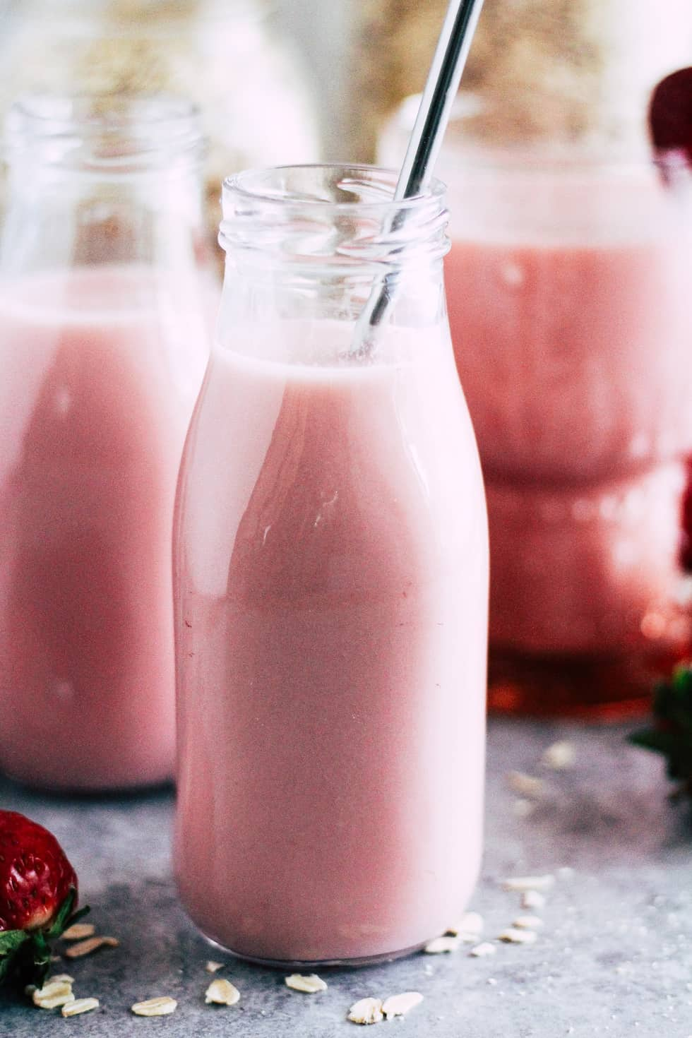 Milk jar filled with strawberry oat milk with a stainless steel straw.