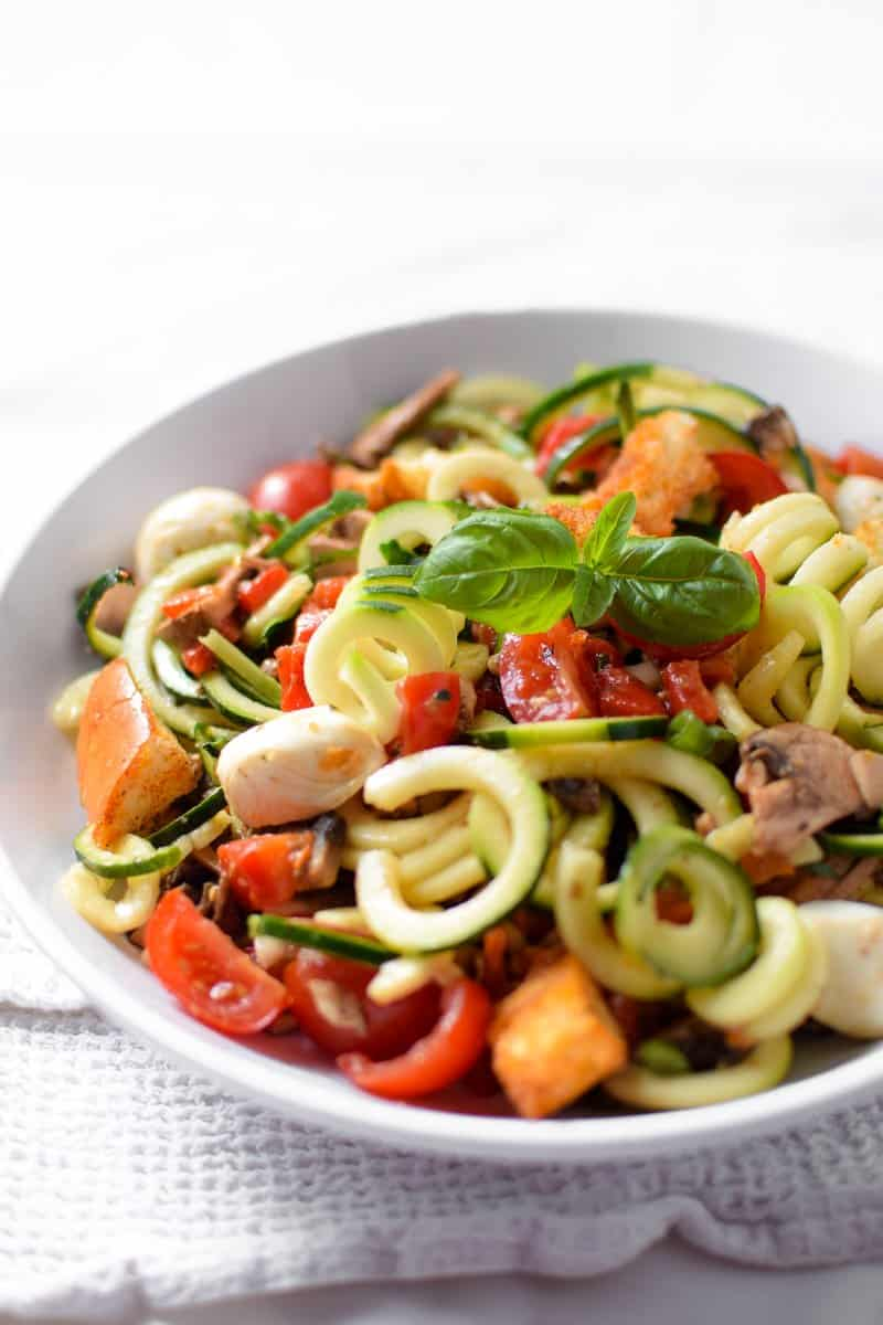 Zucchini noodle salad in white bowl.