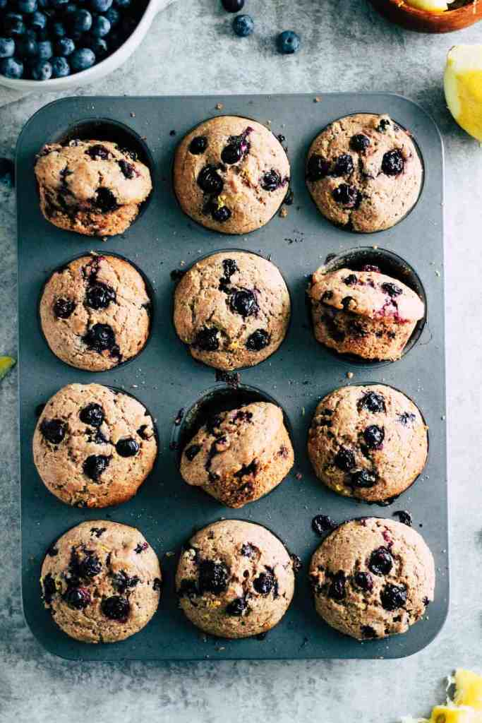 Muffin pan with whole wheat blueberry muffins and bowl of fresh blueberries.