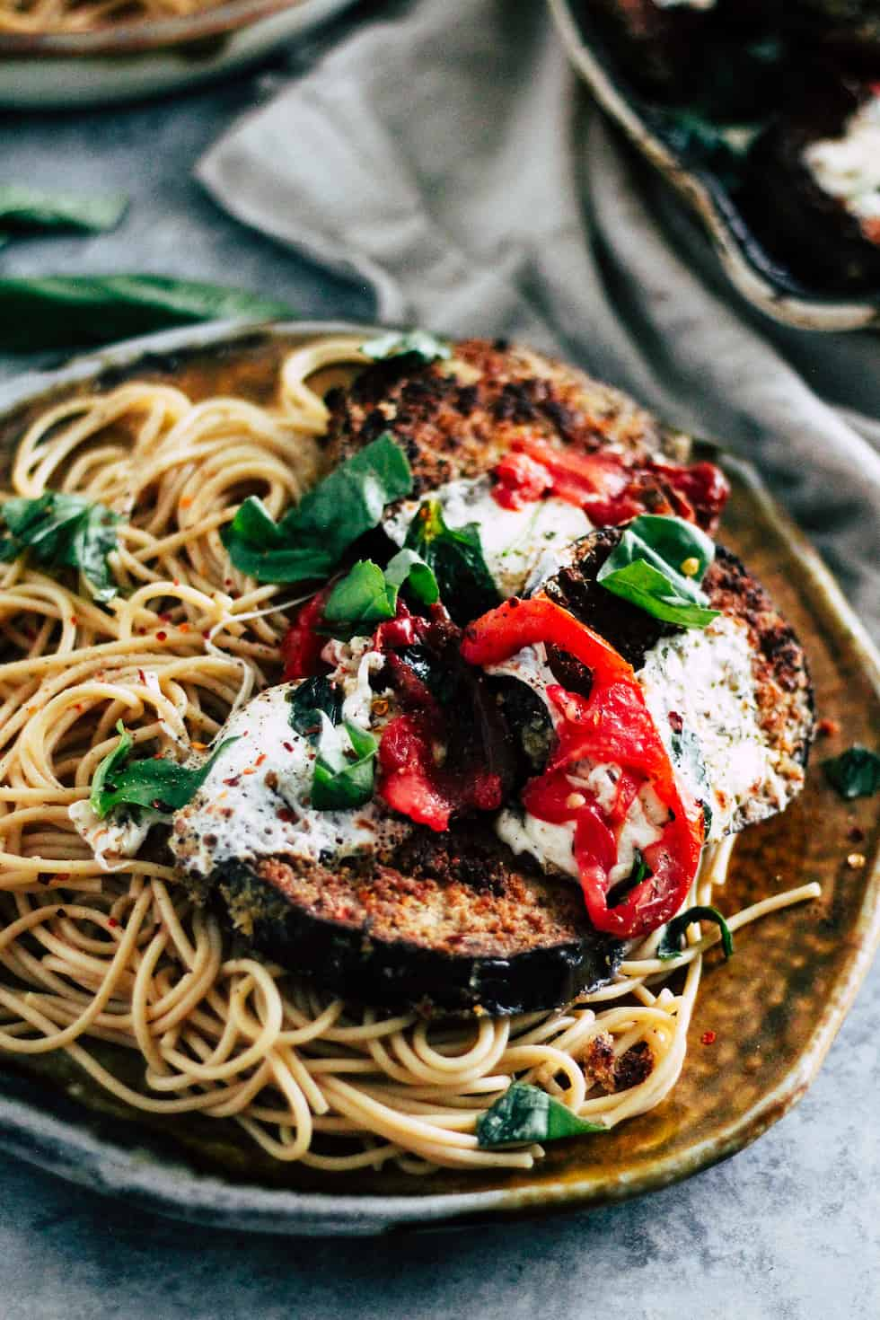 Yellow plate with eggplant over spaghetti.