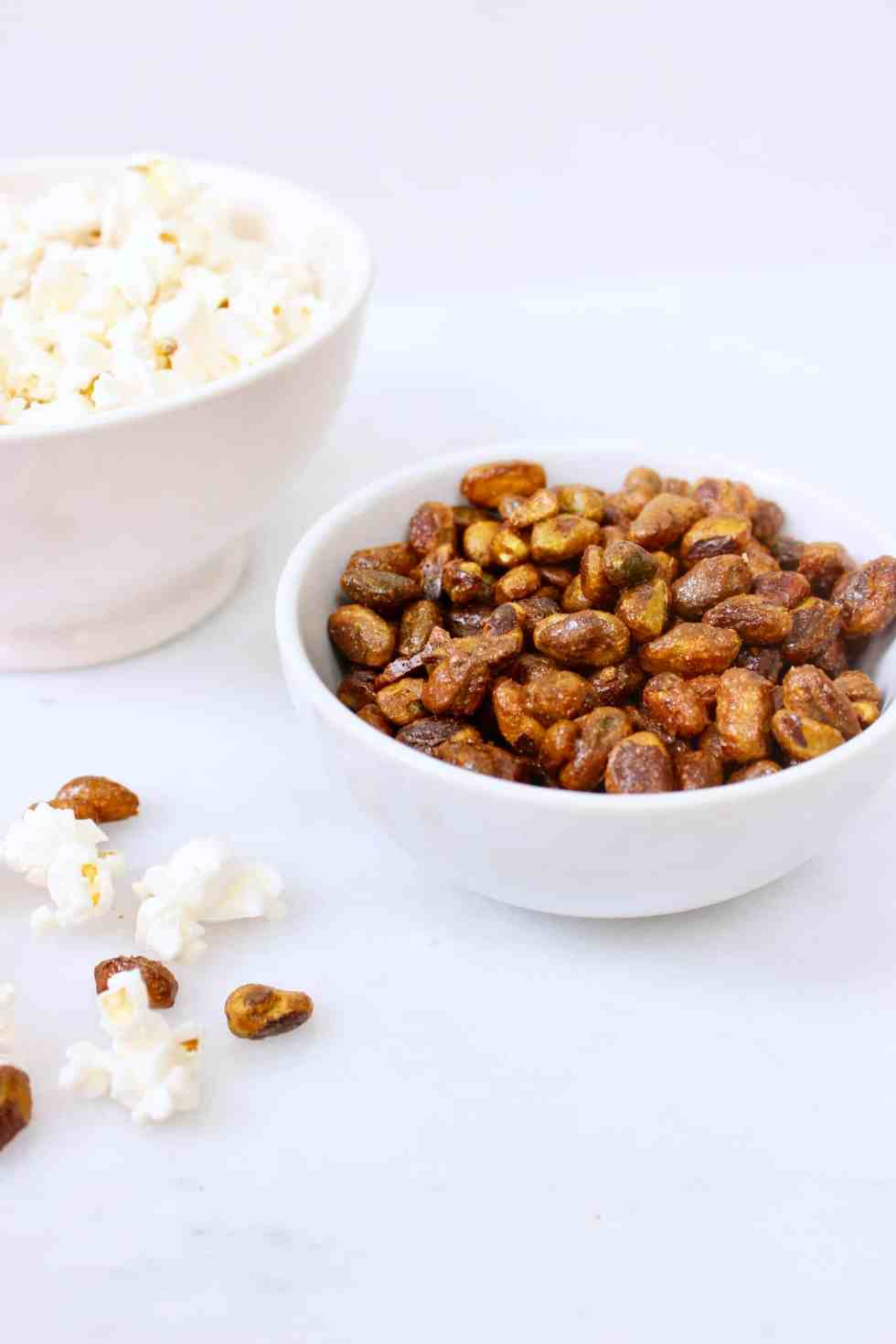 Candied nuts in white bowl against white background.