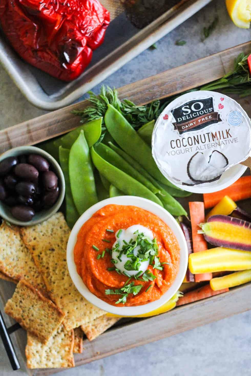 Snack board with So Delicious yogurt alternative and orange dip.