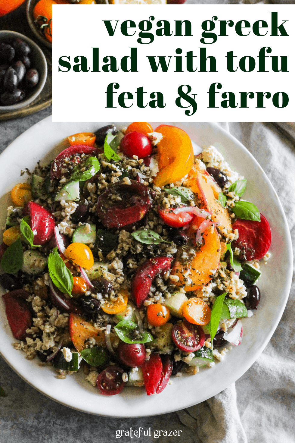 "Tomato and farro salad on white plate with text that reads, ""Vegan Greek Salad with Tofu Feta and Farro."""