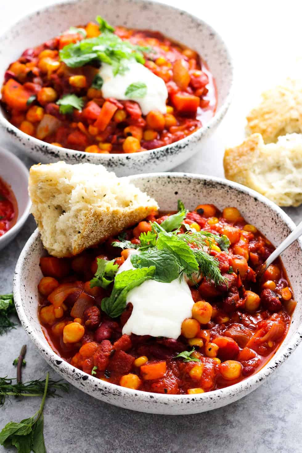 Vegan soup recipes, harissa bean chili in white bowl with bread.