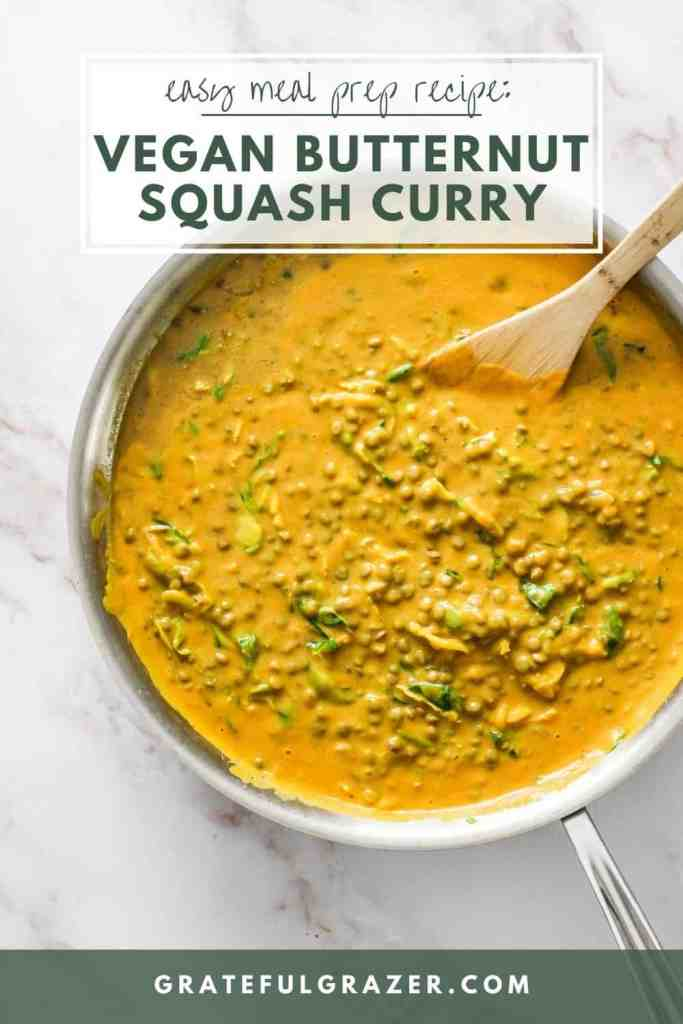 """Yellow curry in a skillet with a wooden mixing spoon. Text reads, """"Easy Meal Prep Recipe: Vegan Butternut Squash Curry. GratefulGrazer.com"""""""