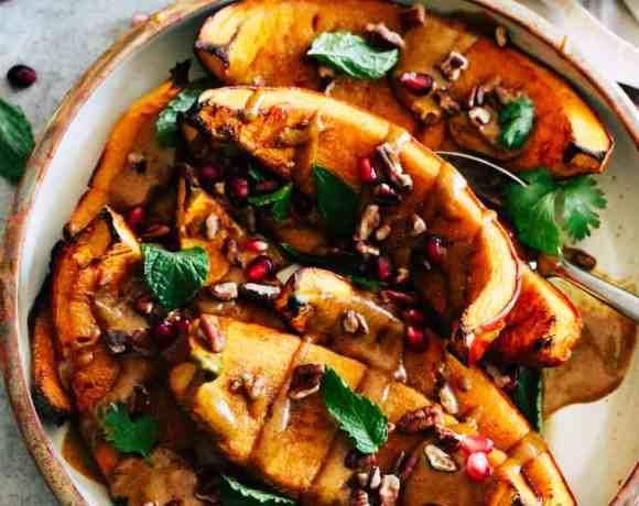Roasted squash in a ceramic dish with yellow curry sauce and toasted nuts.