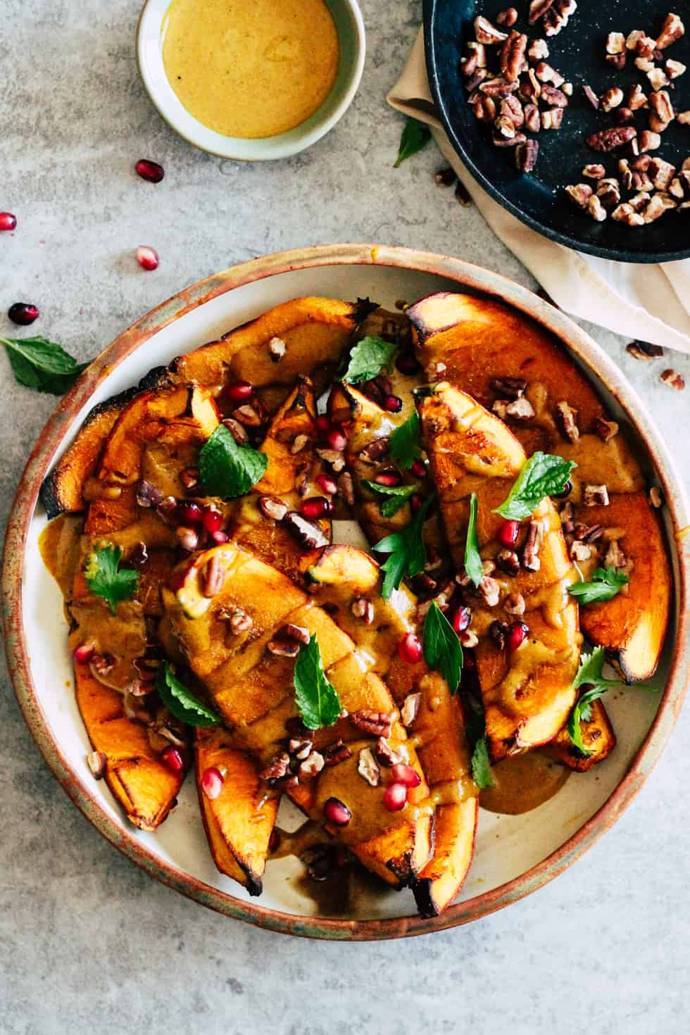 Roasted squash in ceramic dish with toasted pecans and yellow curry sauce.