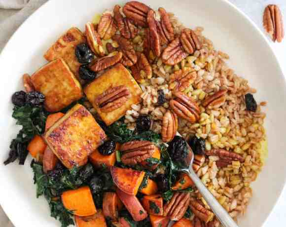 Baked Tofu Bowls with sweet potatoes and kale in white bowl with cream napkin.