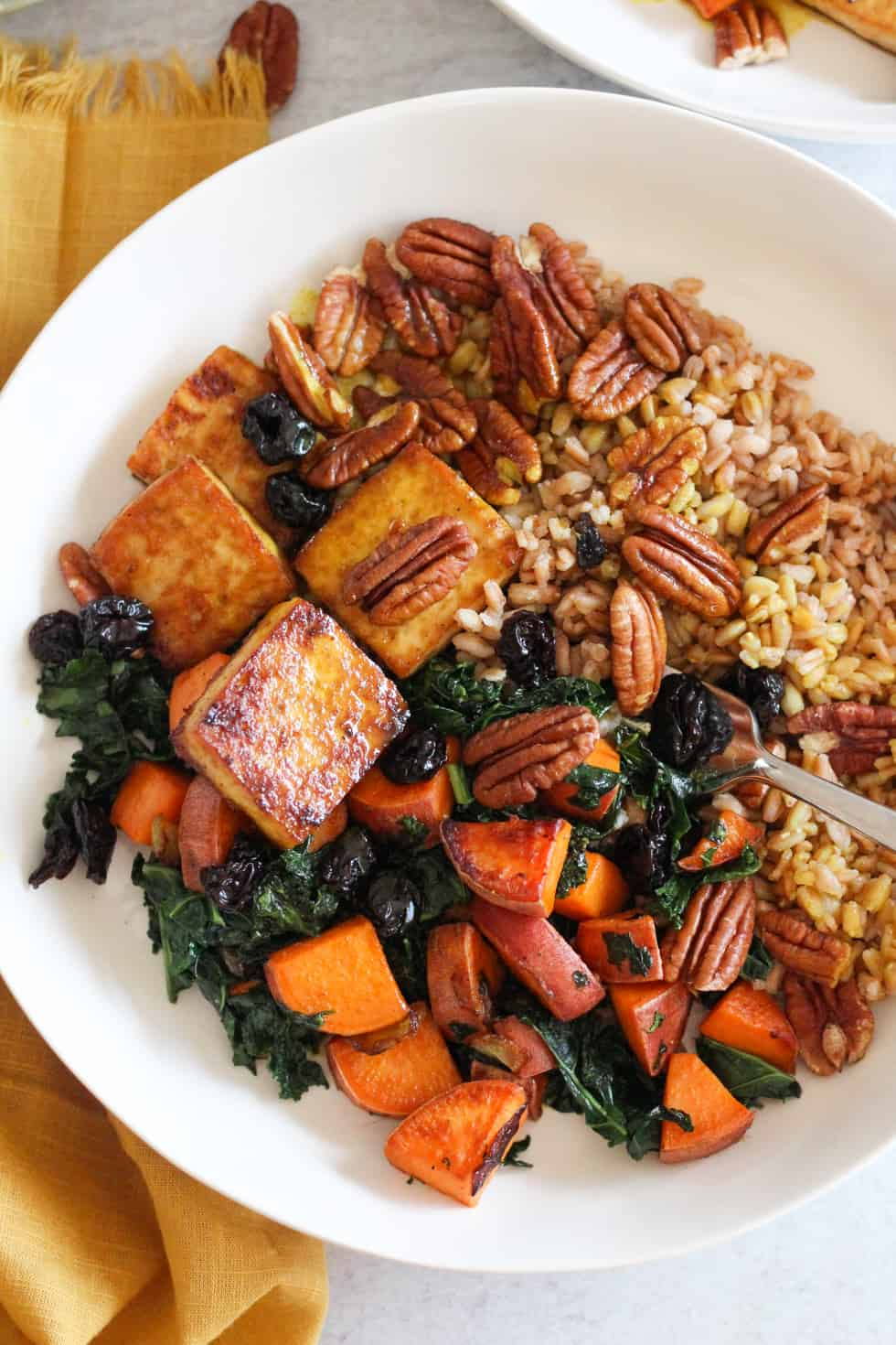Baked tofu bowls with sweet potatoes and kale in white bowl with yellow napkin.
