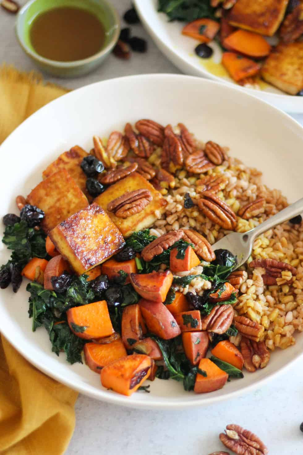 Baked Tofu Bowls with sweet potato and kale in white bowl with yellow napkin.